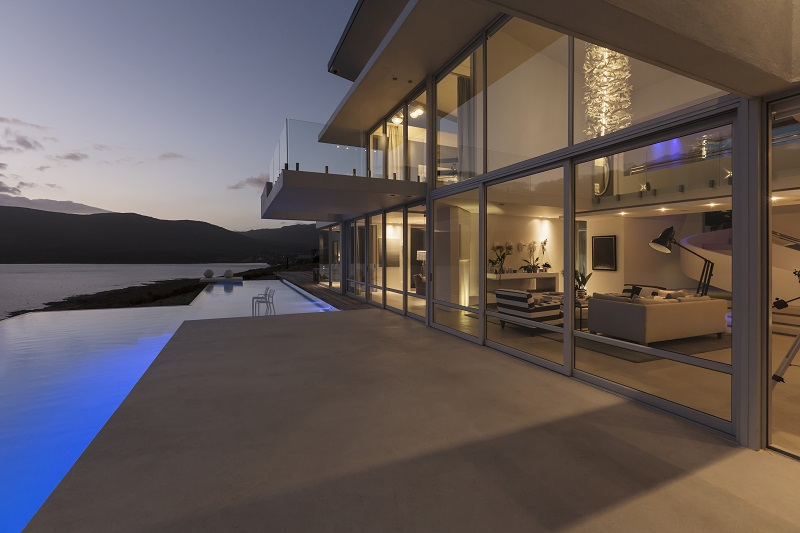 Tranquil modern luxury home showcase exterior with lap pool and dusk ocean view